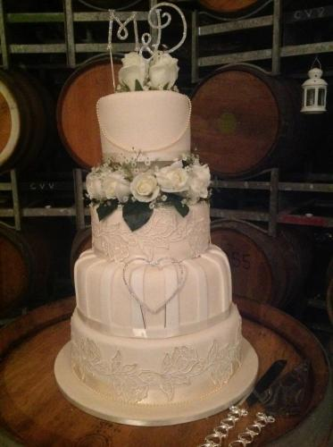 Four Tier Wedding Cake with patterns in icing on each tier.