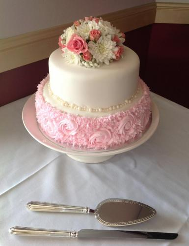 Two tier wedding cake with pink icing on bottom