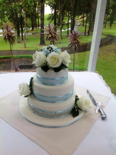 Three Tiered Wedding Cake with blue ribbon and white flowers